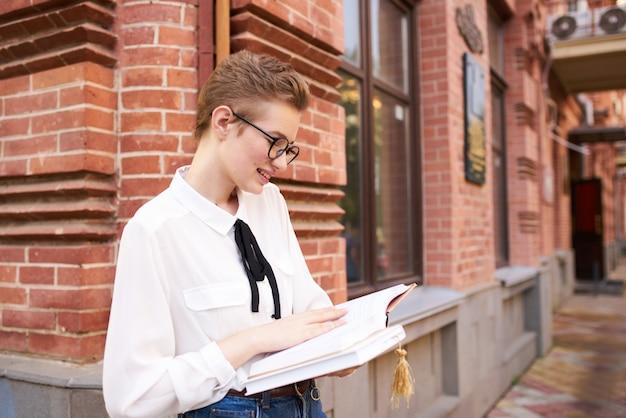 コミュニケーションを読んで屋外で本を手に持っている学生