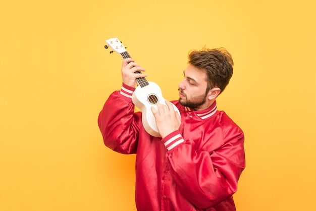 Student with a beard is isolated on yellow with a ukulele in his hand.
