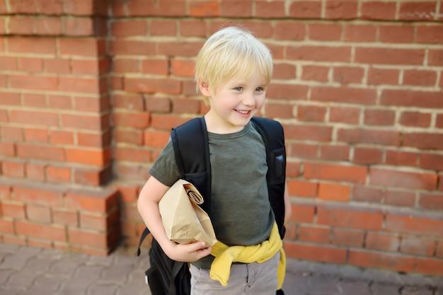 校舎近くの大きなバックパックとランチバッグを持つ学生。