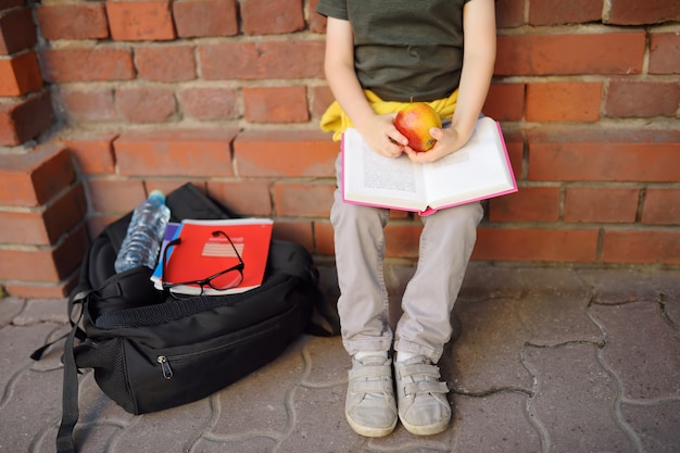 Student with big backpack and lunch bag sat down to eat his lunch near the school building.