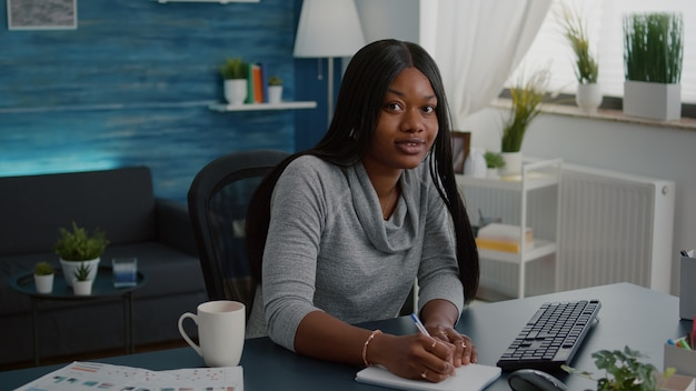 Student with black skin browsing online courses writing school homework on notebook