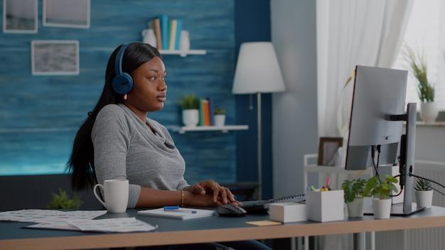 ヘッドフォンを持っている黒い肌の学生は、リビングルームの机に座っているeラーニングプラットフォームを使用してオンラインの大学のコースを聞いています