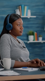 Student with black skin having headphone puts listening online univeristy course