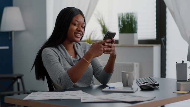 Student with black skin texting message using modern phone while sitting at desk working remote from home