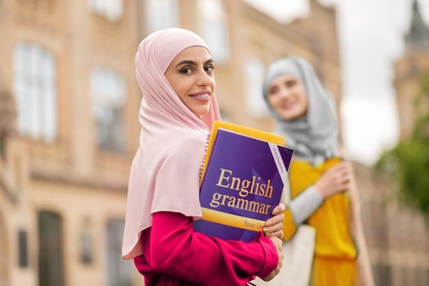 책을 가진 학생. 영문법 책을 들고 검은 눈을 가진 매력적인 스마트 무슬림 학생