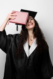 졸업 가운과 모자 대학을 마칠 준비가 된 학생. 검은 가운 웃 고있는 학자 젊은 여자.