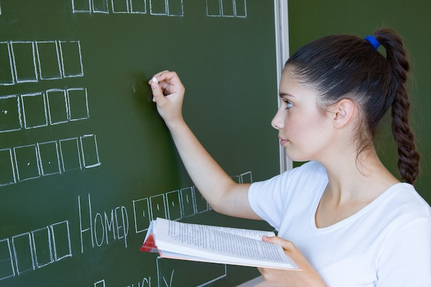 Student with book stays near blackboard in classroom