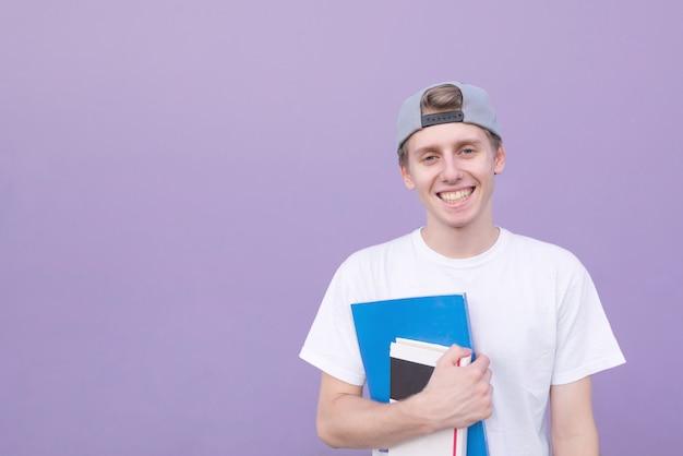 Студент с книгами и блокнотом в руках, изолированных на фиолетовом фоне