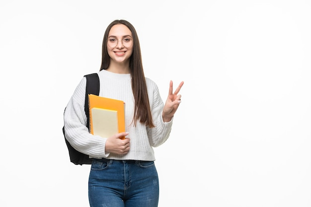 흰 벽에 평화 제스처가 있는 책과 배낭을 든 학생. 시험 준비