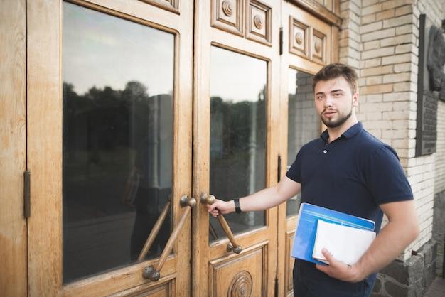 本とノートを手に持った学生は大学への扉を開き、カメラを見ています。