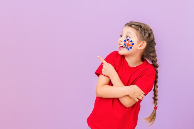 A student with a british flag painted on her cheek points her fingers to the side and smiles.