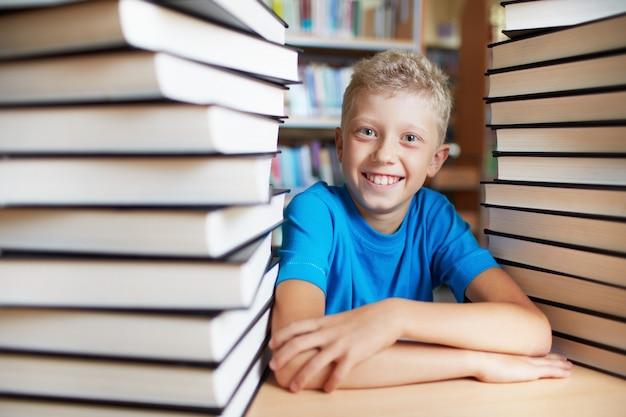 テーブルの上に交差した腕を持つ学生
