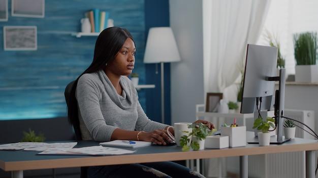 Eラーニング大学プラットフォームを使用したマーケティングオンラインコースで自宅から離れた場所で作業している肌の色が濃い学生