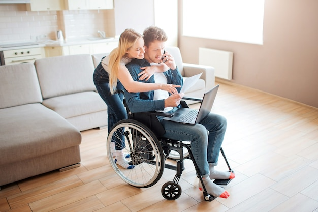 Student with disability sitting on wheelchair. cheerful woman stand behind and embrace him. looking on laptop. young man with special needs. couple together