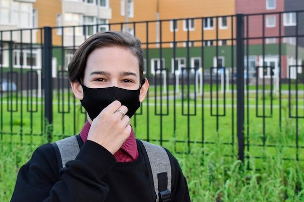 学校の前に立っているフェイスマスクを持つ学生
