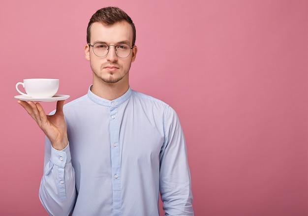 眼鏡の学生はコーヒーのマグカップで休んでいます。