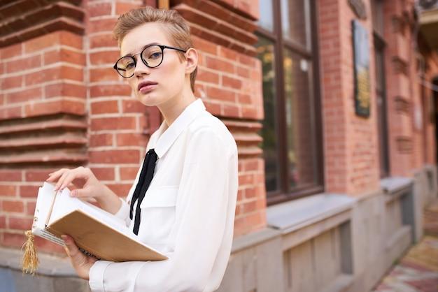 책 생활 방식으로 도시를 산책하는 안경을 쓴 학생