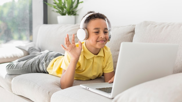 Student with headphones waving at laptop