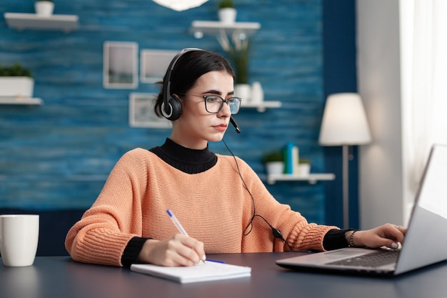 Student with headphones writing notes on notebook while searching communication information using laptop computer. concentrated teenager making homework while sitting at desk in living room