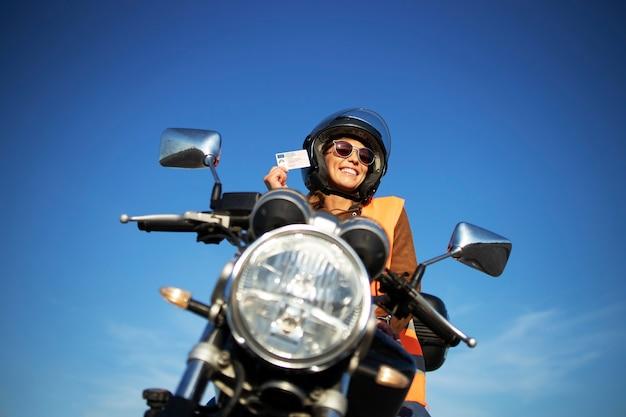 Студент со шлемом и светоотражающим жилетом катается на мотоцикле в классе.