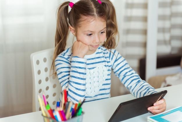 Студент с планшетом, книгами и бумагами, учится дома