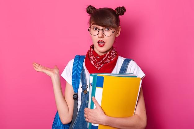 2つの房を持つ学生、tシャツ、オーバーオール、バンダナを着て、紙フォルダーを持ち、手のひらを脇に置き、驚いた表情、ピンクの上に口を開けてポーズをとった。