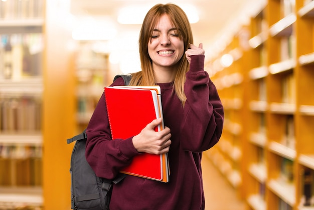 Student woman covering her ears on unfocused background. back to school