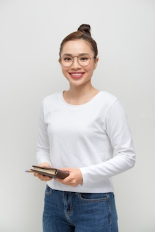 Student woman holding a notebook for notes in the hands