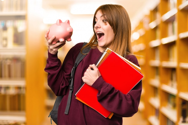 Student woman holding a piggybank on unfocused background. back to school