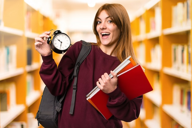 Student woman holding vintage clock on unfocused background. back to school