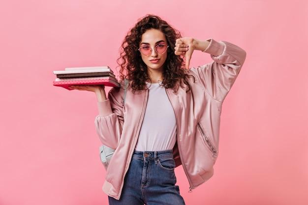 Студентка в розовых очках держит книги и показывает палец вниз