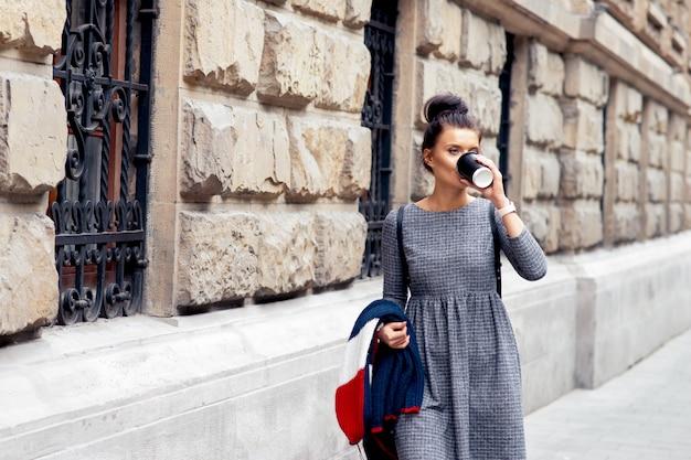 Студент женщина пьет из бумажного стаканчика возле каменной стены университета.