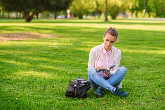 Student woman is studying outdoors in university campus at sunset.