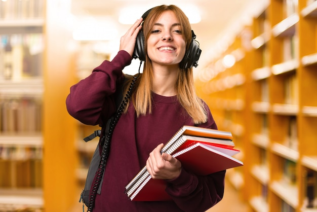 Student woman listening music on unfocused background. back to school