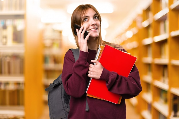 Student woman talking to mobile on unfocused background. back to school