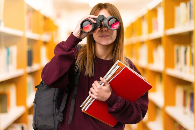 Student woman with binoculars on unfocused background. back to school