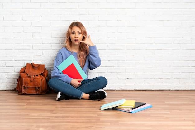 屋内の床に座って電話ジェスチャーをしているピンクの髪の学生女性。コールバックサイン