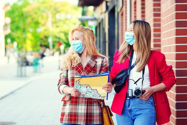 Студенческие женщины вместе исследуют новый город. летние каникулы во время пандемии коронавируса. туристы в медицинских масках.