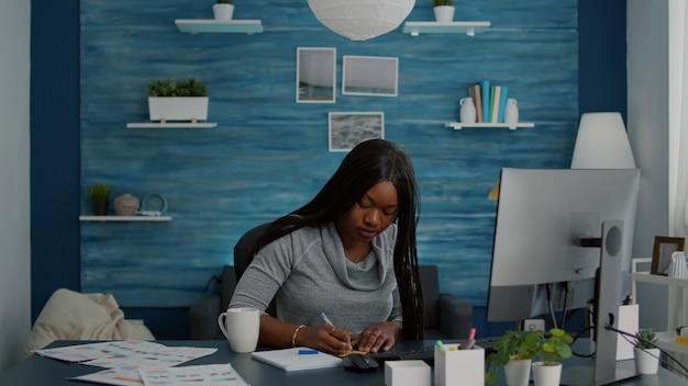 대학 온라인 과정에서 e 러닝 플랫폼을 사용하여 학교 숙제에서 작업하는 컴퓨터에 스티커 메모에 비즈니스 아이디어를 쓰는 학생