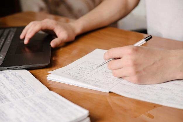 Студент пишет содержание на бумажном блокноте с ручкой во время изучения онлайн-курса через портативный компьютер на деревянном столе.