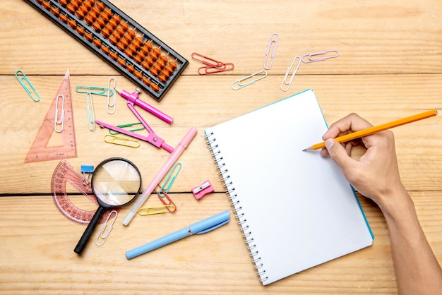 Student writing in notebook with school supplies and stationery on the wooden table