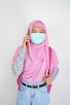 学生の若い女の子は、白い背景の上の携帯電話を使用してマスクを着用します
