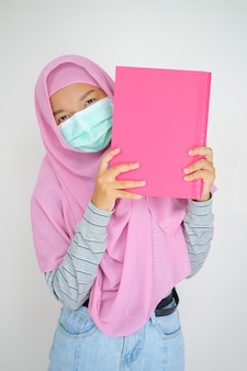 学生の若い女の子はピンクのヒジャーブとマスクを身に着けている白い背景の本を保持します