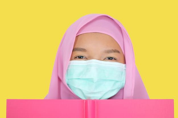 学生の若い女の子は黄色の背景にピンクのヒジャーブとマスクを着用します。