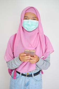 学生の若い女の子はマスクを着用し、白い背景の上の携帯電話を使用してイスラム教徒の女の子