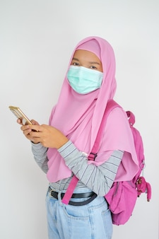 Student young girl wears a mask and uses a mobile phone on white background a muslim girl