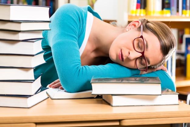 학생-책을 배우는 도서관에서 젊은 여성, 그녀는 자고 피곤하며 과로입니다.
