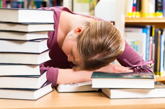 Студент - молодая женщина в библиотеке с изучением книг, она спит, устала и перегружена