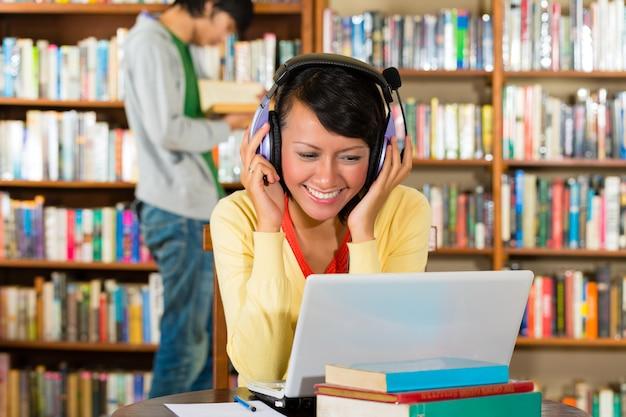 Студент - молодая женщина в библиотеке с ноутбуком и наушниками обучения