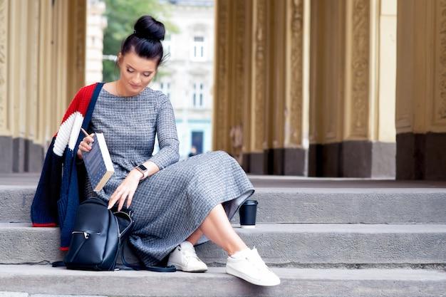 Студент молодая женщина кладет книгу в рюкзак.